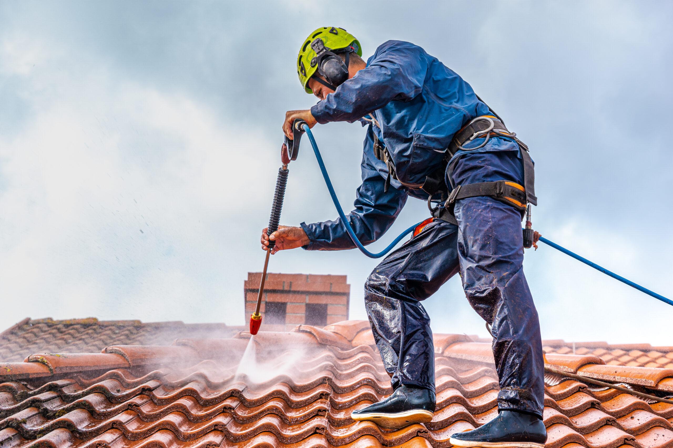 Ouvrier en cours de démoussage de toiture